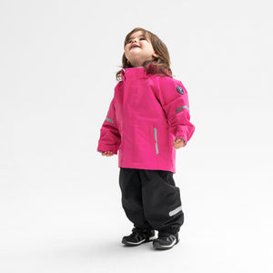 Little girl sporting a pink, kids waterproof jacket, paired with black, kids waterproof trousers, made of shell fabric.