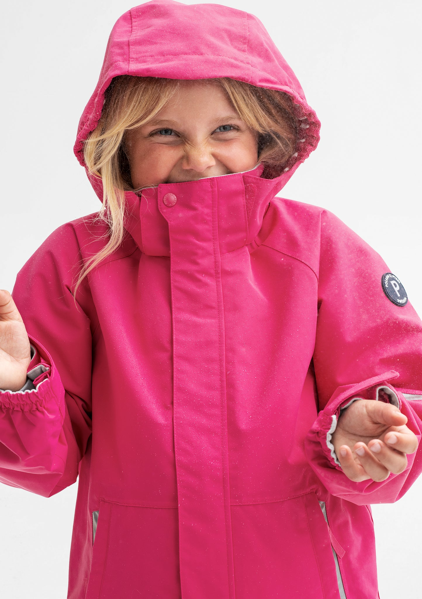 A young girl wearing a pink, kids waterproof jacket with detachable hood and adjustable cuffs, made of soft shell fabric.