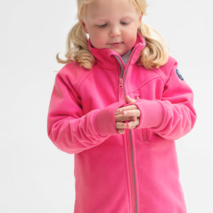 A young girl wearing a pink, kids waterproof fleece jacket, with reflector zips & cuff thumbholes, made of breathable fabric.