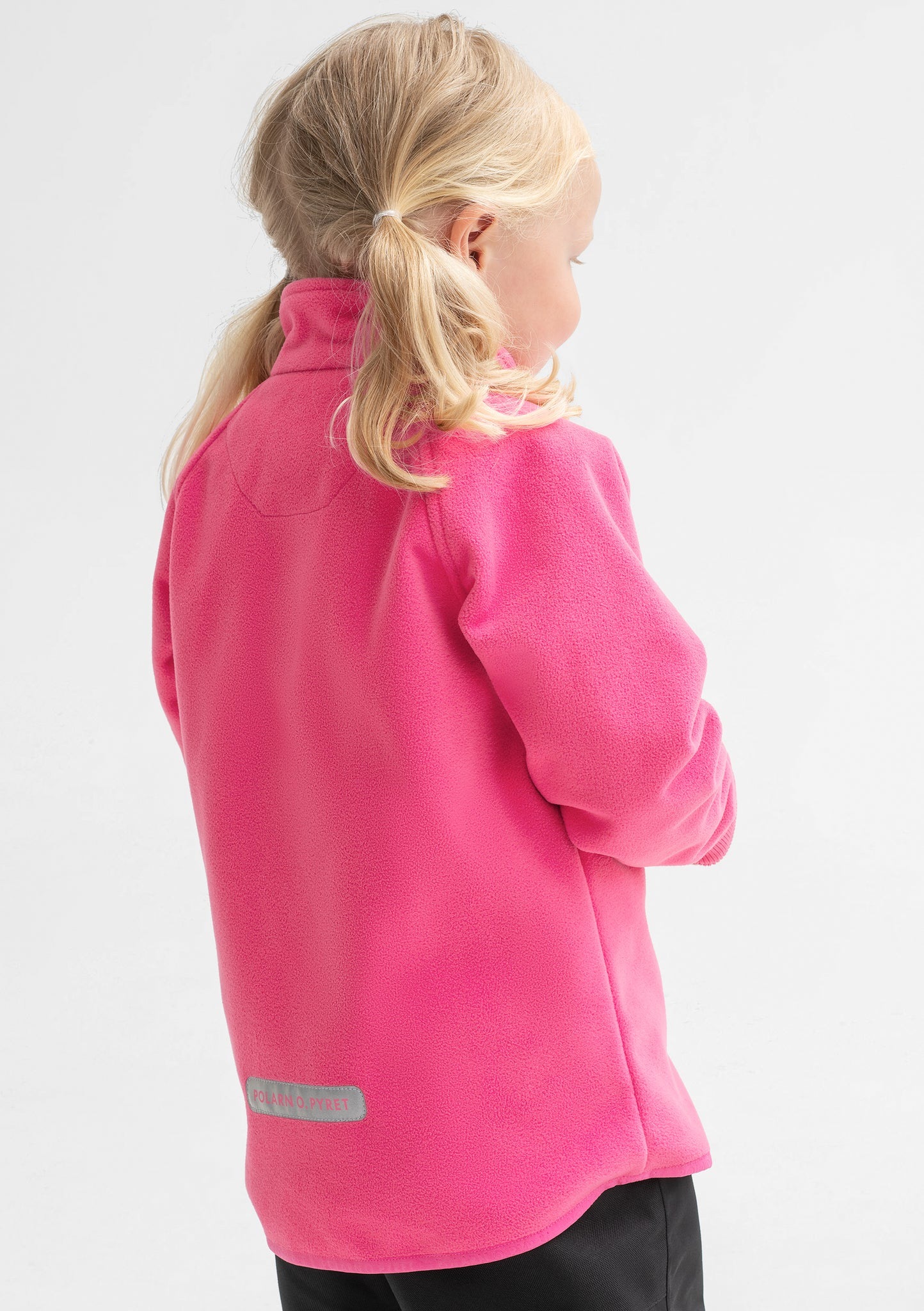 Side view of a young girl wearing a pink, kids waterproof fleece jacket, with cuff thumbholes, made of soft fabric.