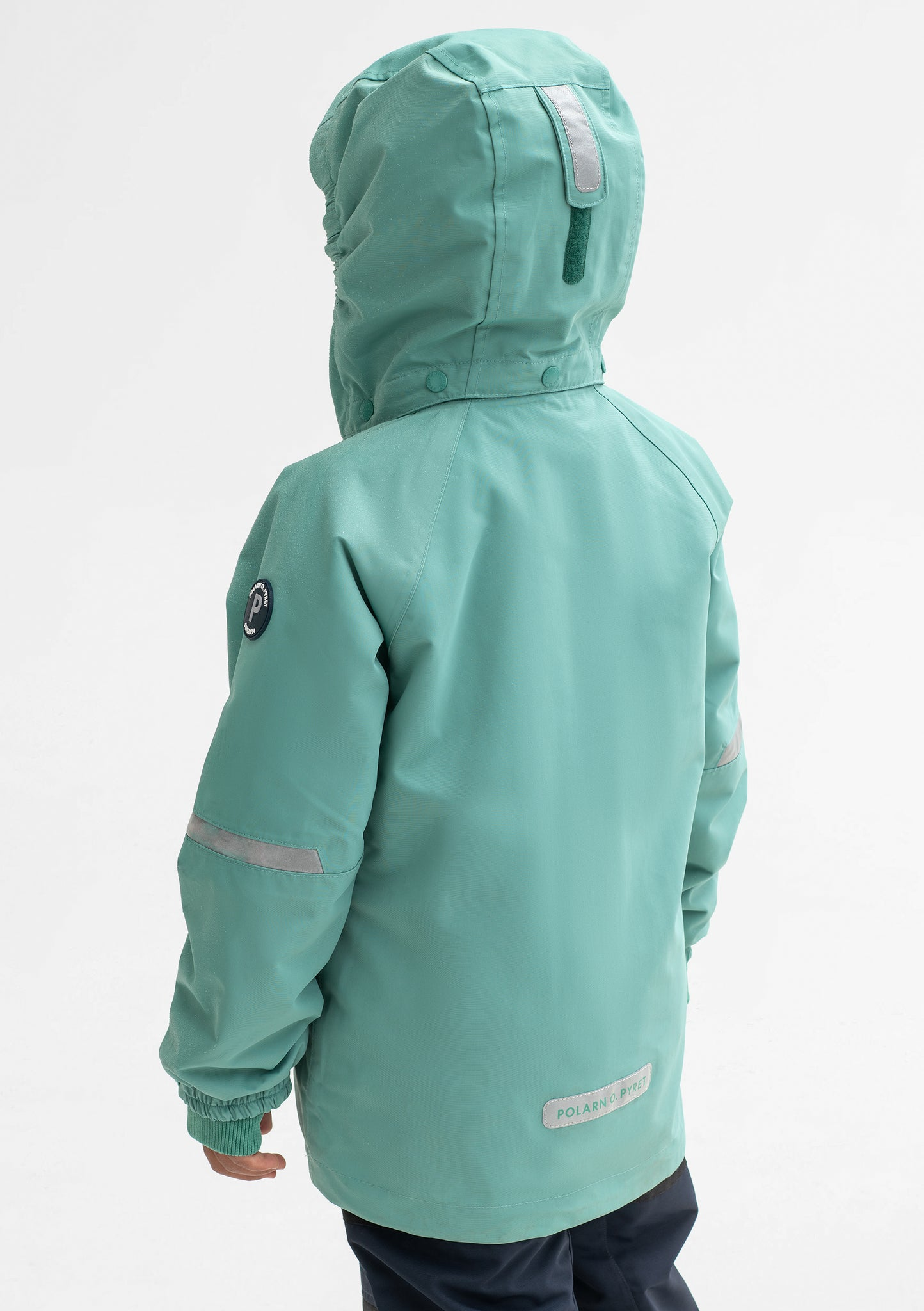 Back view of a boy wearing a green, kids waterproof jacket made of lightweight fabric, with silver reflectors on the sleeves.