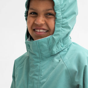 A boy smiling, wearing a green, hooded waterproof shell jacket, made of durable and lightweight fabric.