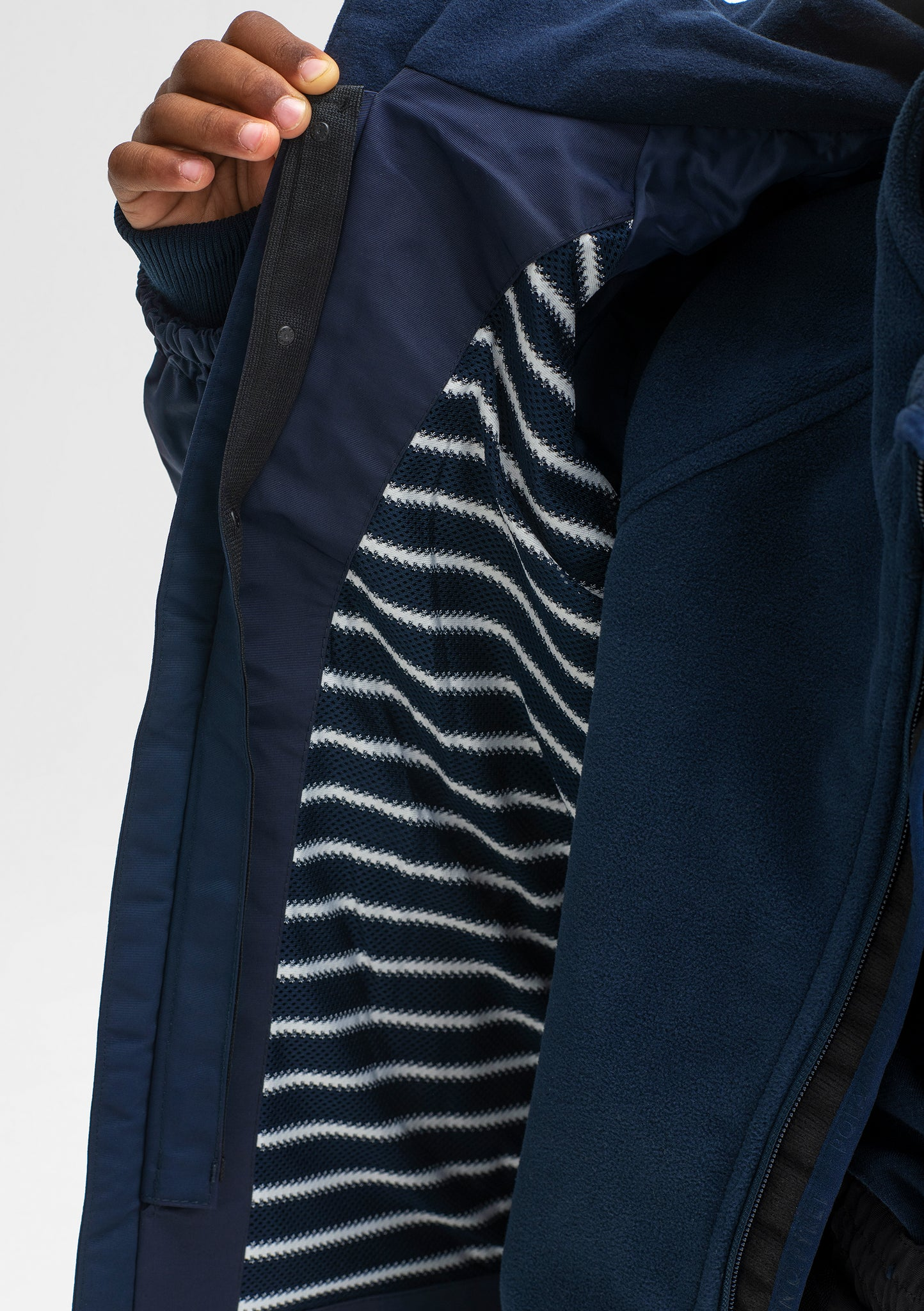 Close up shot of the striped inner lining of kids waterproof jacket in the colour navy, made of lightweight shell fabric.