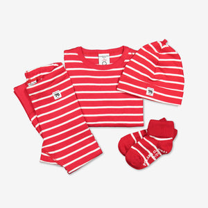 A set of red and white stripe print organic cotton baby outfit, featuring a babygrow, a pair of leggings, socks and a hat.