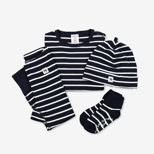 Whole set of cotton baby outfits in navy blue and white stripe, including a babygrow, a hat, leggings and a pair of socks.