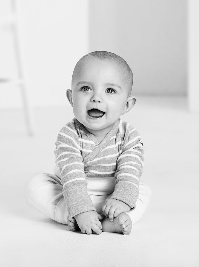 Black and white photo of a baby wearing a grey and white striped wraparound babygrow made from organic cotton material.
