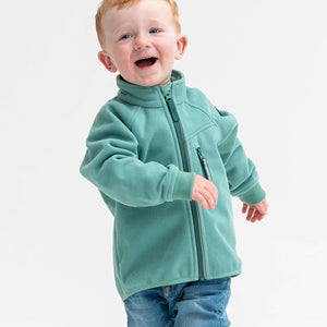 A young boy wearing a green, kids waterproof fleece jacket, with reflector zips and fit cuffs, made of breathable fabric.