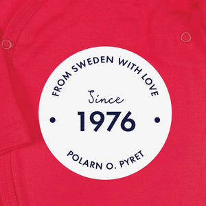 "White round logo with 'From Sweden With Love, Since 1976"" text, shown on a red organic cotton babygrow background."