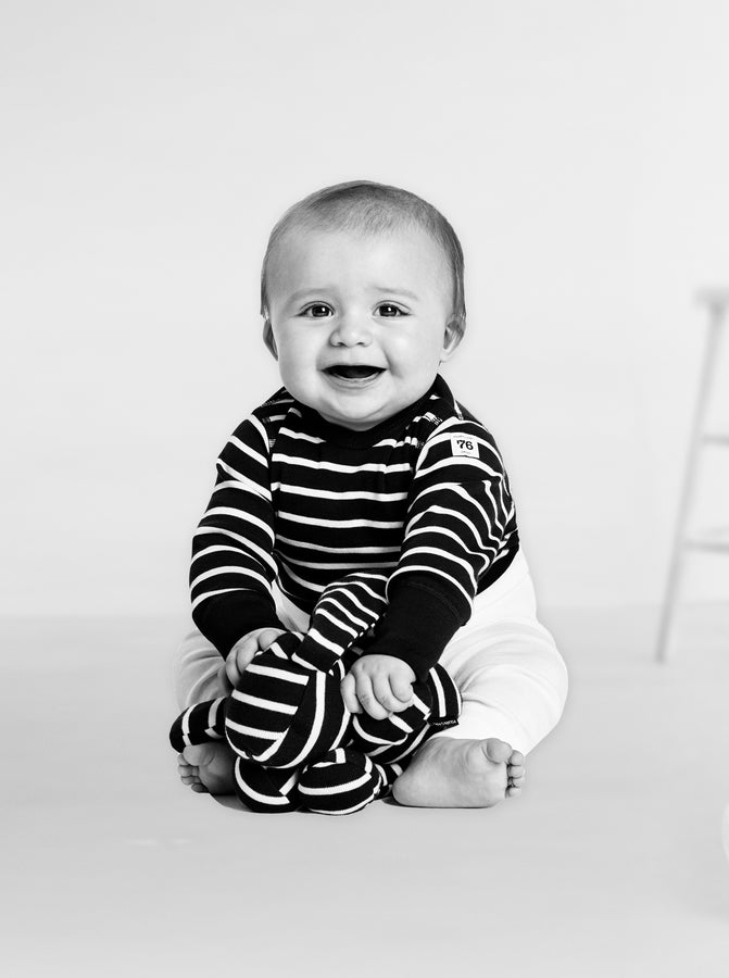 Black and white photo of a baby wearing a stripe print babygrow paired with white leggings and holding a stripe print rabbit.