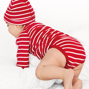 A crawling toddler wearing an organic cotton babygrow, paired with a hat in a classic red and white stripe print.