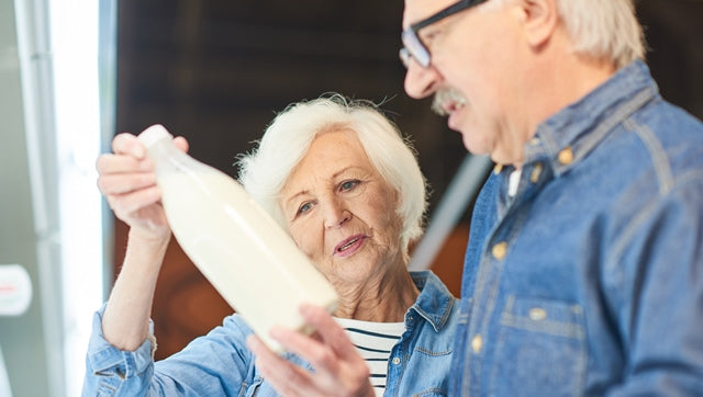 a senior couple checking the ingredient label of milk