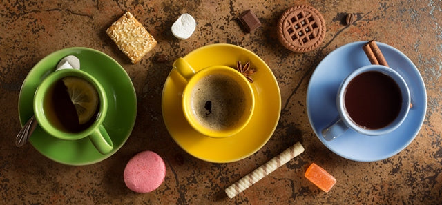 cups of coffee and tea surrounded by sweets