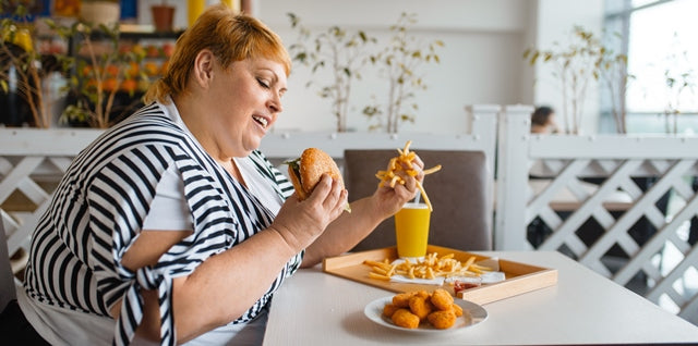 obese woman eating processed foods like burger and fries