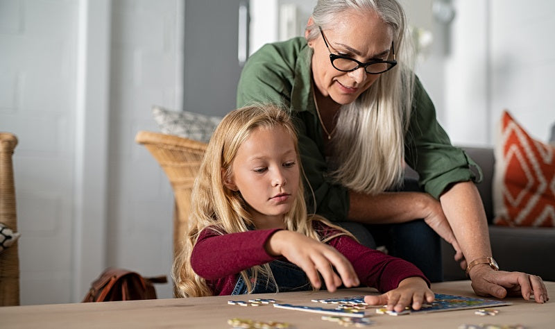 grandmother and granddaughter solving a puzzle