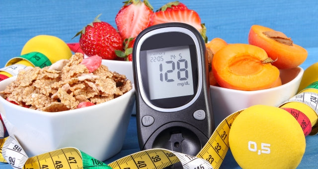 glucometer surrounded by fruit and dumbbells