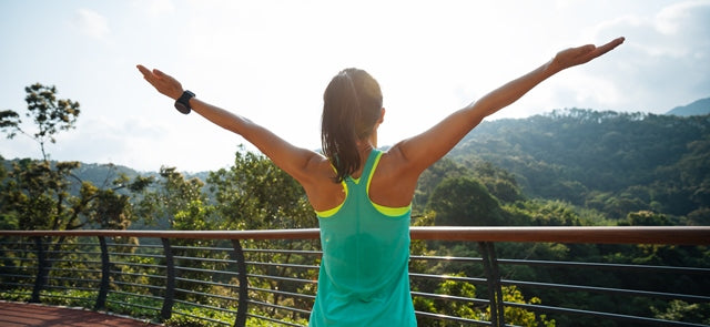 woman in workout gear looking out to a beautiful view