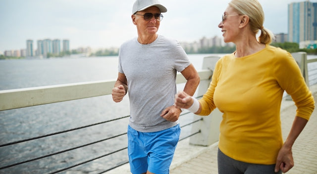 two seniors lightly jogging along the river
