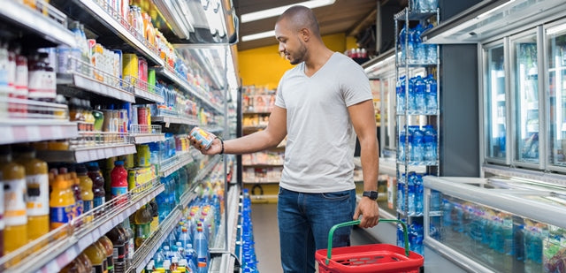 man looking at a can in a grocery store