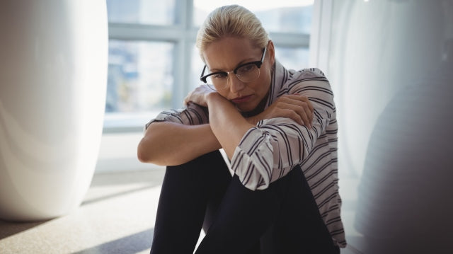 sad blonde woman with glasses