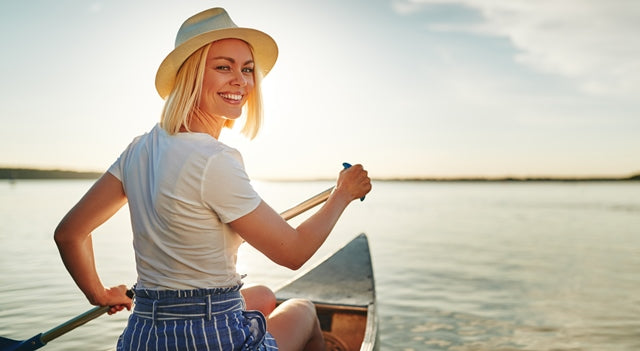 happy woman in a canoe at sunset