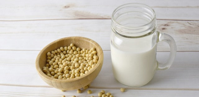 a bowl of soy beans with a mason jar of soy milk