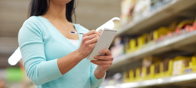 woman checking off shopping list items