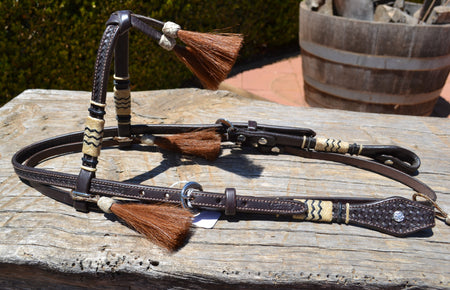 Collection image of Vaquero Brand Jose Ortiz Futurity Browband headstall with hand braided natural rawhide  with black detail and chestnut horsehair tassels.