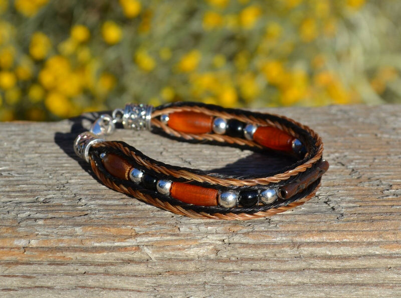 "Close Up View Awesome 3/8"" wide, 3 Strand Braided Horsehair Bracelet with a lobster claw clasp and various colored and patterned bone beads. Chestnut/Black/Silver"