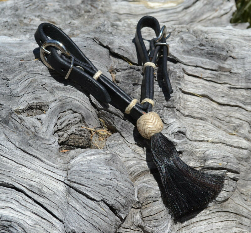"Jose Ortiz handmade 1/2"" black harness leather curb strap with tightly braided natural rawhide knot and black mane horsehair tassel."