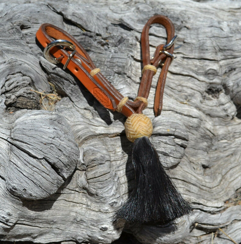 "1/2"" light russet oil leather curb strap with tightly braided natural rawhide knot and black mane horsehair tassel."