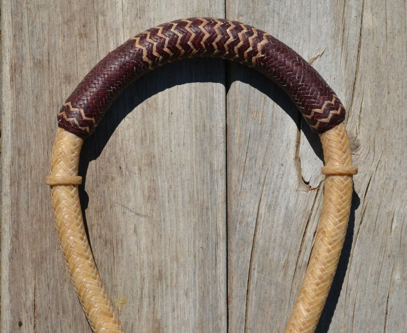 "Close Up View Bosal Jose Oritz 5/8"" hand braided natural rawhide bosal with latigo leather on nose and round shaped knot with natural rawhide details.  This bosal has 18 plait cheeks over a flexible all rawhide core."