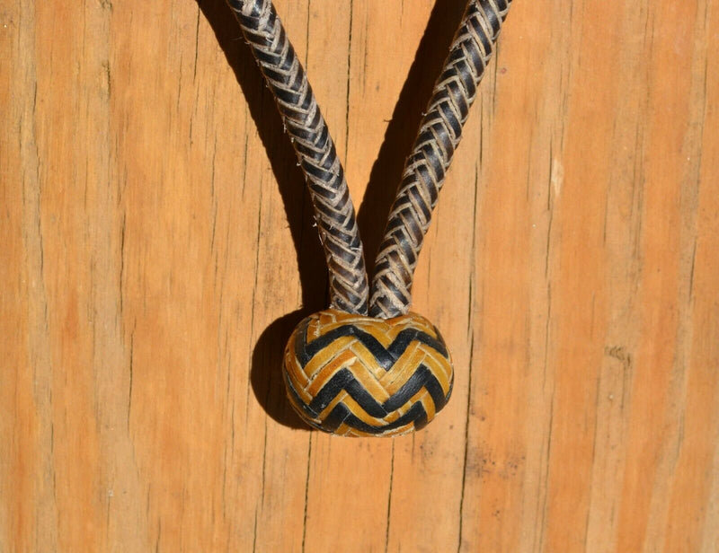 "Knot Detail Jose Oritz 1/4"" 8 plait braided brown beveled rawhide bosal with natural rawhide nose and knot with black details.  Noseband measures 3/8"" wide at the thickest point."