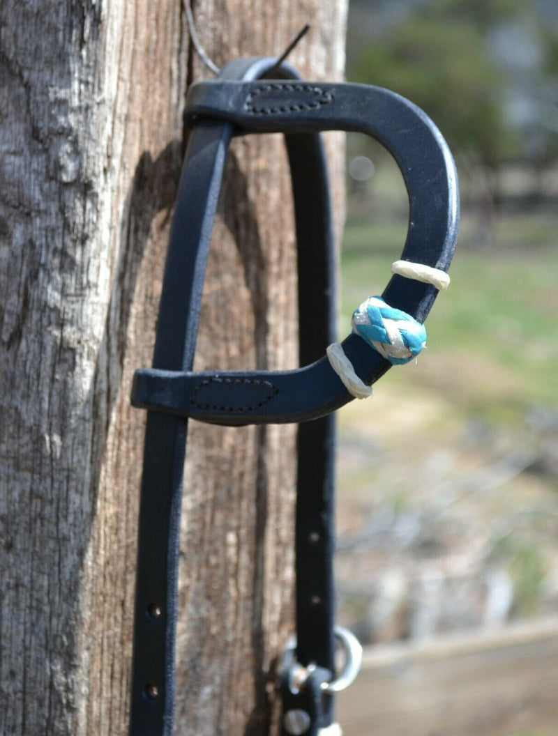 "One Ear Rawhide Detail View Jose Ortiz 5/8"" One/Single Sliding Ear Headstall.  Constructed of single-ply black harness leather.  Hand braided natural rawhide with turquoise details on cheeks and ear piece."