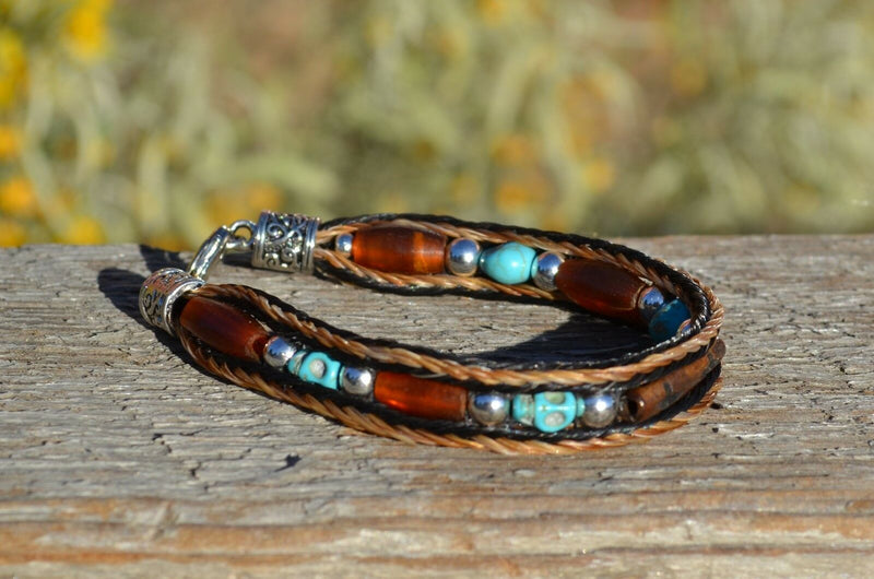 "Close Up View Awesome 3/8"" wide, 3 Strand Braided Horsehair Bracelet with a lobster claw clasp and various colored and patterned bone beads. Chestnut/Black/Turquoise/Skull"