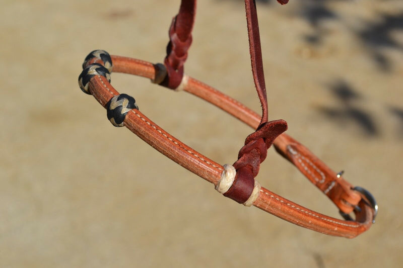Close Up View Jose Ortiz has made these beautiful rolled harness leather adjustable western training cavesons with latigo hangers.   Made from beautifully conditioned Hermann Oak harness leather with 3 natural and black and natural rawhide knots over the nose and natural rawhide hanger knots.