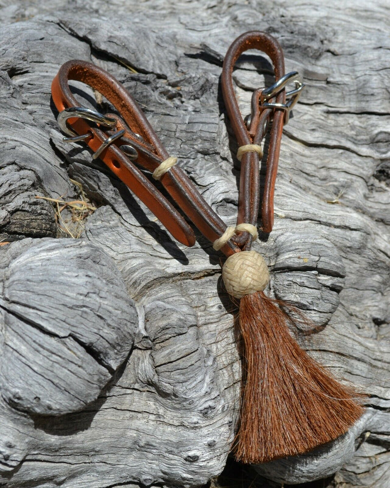 "1/2"" light russet oil leather curb strap with tightly braided natural rawhide knot and chestnut mane horsehair tassel."