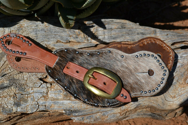 Close Up View Cowboy Style Hair-On Cowhide Shaped Spur Straps.  Hair-on cowhide with grey & brown brindle coloring with stainless steel spots.  Soft distressed leather lining and Hermann Oak harness leather straps.  Brass buckles.