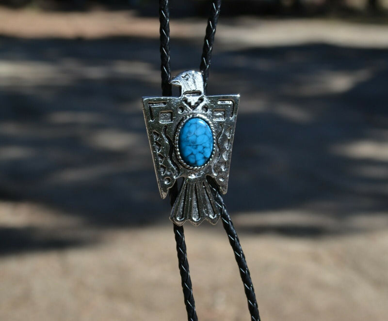Close Up View Western Style Black Braided Leather Bolo Tie with Thunderbird Slide with turquoise color stone and silver tips.