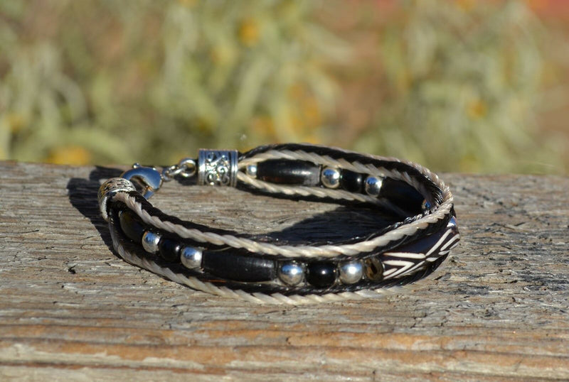 "Close Up View Awesome 3/8"" wide, 3 Strand Braided Horsehair Bracelet with a lobster claw clasp and various colored and patterned bone beads. White/Black/Black"