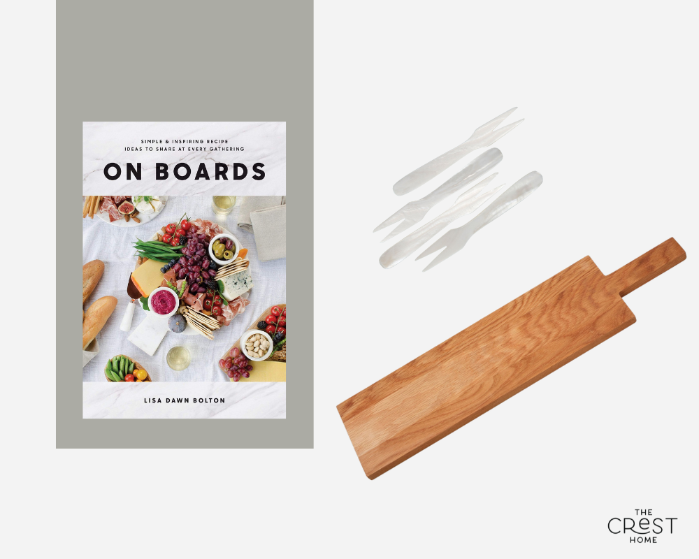 """A collage of a book, a set of four small mother-of-pearl forks, and a long rectangular wooden board with a handle. The book is titled """"On Boards"""" and shows a top-down view of charcuterie."""