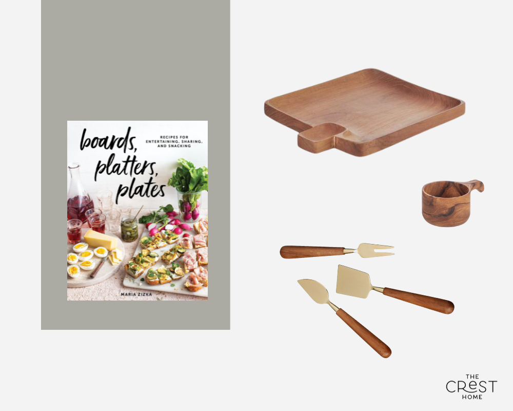 """A collage of a book, a square wooden tray with an indented area, a wooden scoop, and a set of utensils with wooden handles. The book's title is """"Boards, platters, plates"""" and has images of charcuterie."""