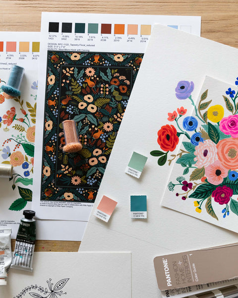 Several paintings of gouache on paper are scattered on a table. They feature floral designs in many colors. There are spools of thread, tubes of paint, and color samples arranged on top.