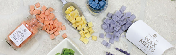 Many cubic wax melts of different colors are on a flat surface, pouring out of a jar, a scoop, and a paper pack.