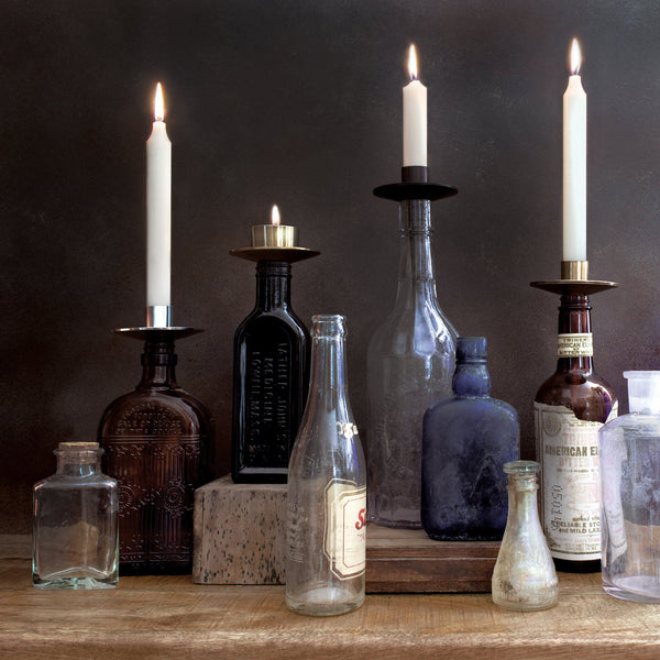 Several glass bottles of varying styles and colors are arranged on a table. They have candle holders inserted in the top, with white, lit taper candles.