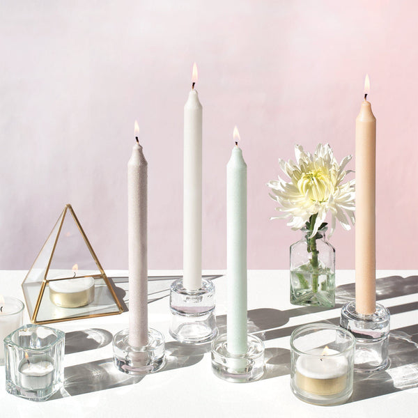 Several pastel colored taper candles with a shimmery texture are placed in candle holders. They are surrounded by various decor items, such as a pyramid glass terrarium and a vase with a daisy.