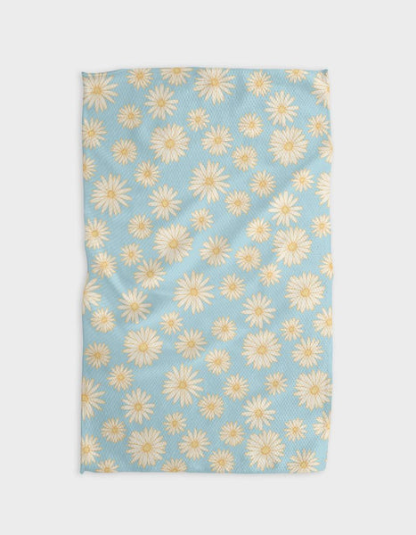 A rectangular, light blue tea towel with daisies all over it. The daisies have white petals and yellow centers.