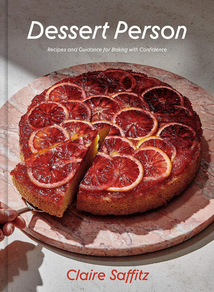 """A book cover, the top section says """"Dessert Person"""" and the bottom says """"Claire Saffitz"""". Pictured is a one-layer cake with blood orange slices on top. One slice has been cut and is being lifted off of the wood board it's placed on."""