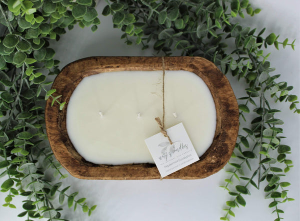 A top-down view of a  candle in an oval wooden bowl that has three wicks and a tag attached by a string. It sits on a background of eucalyptus.