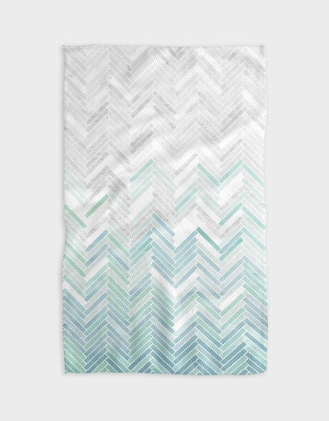 A rectangular with a chevron pattern. The pattern has a color gradient, it is aqua colored on the bottom fades into light grey on the top.
