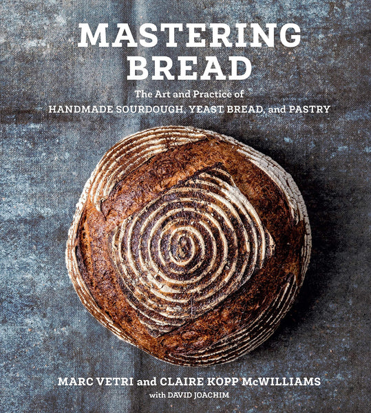 """A book cover with a top-down view of a baked, circular loaf of bread on a grey background. The top says """"Mastering Bread"""""""
